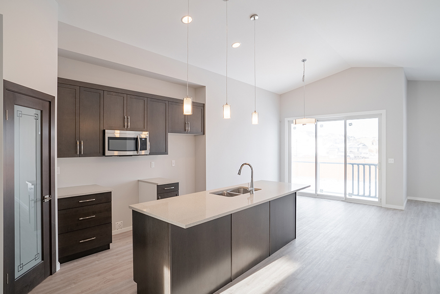 3. Kitchen with dark wood maple cabinets, island, hanging pendant lights and quartz countertops - 159 Atlas Crescent The Highview DG 43 A Broadview Homes