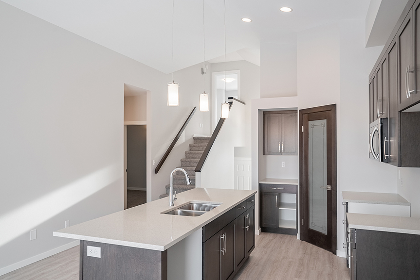 5. Kitchen with dark maple cabinets, quartz countertops, hanging pendant lights above island and light grey painted walls - 159 Atlas Crescent The Highview DG 43 A Broadview Homes