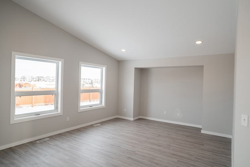 7. Great Room with vinyl plank flooring, light grey painted walls, large windows, vaulted ceilings and white casing and baseboards - 159 Atlas Crescent The Highview DG 43 A Broadview Homes