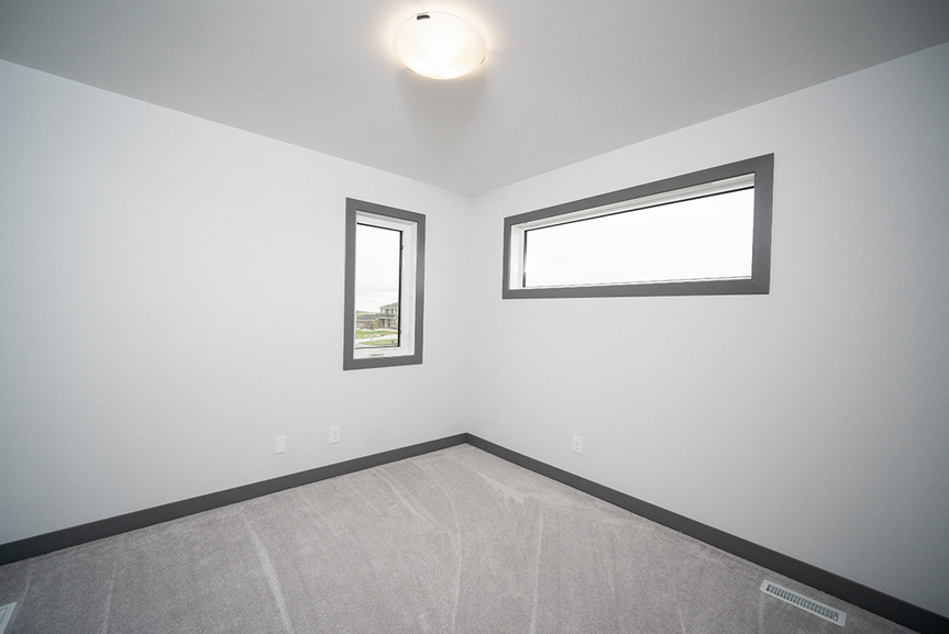 10. Bedroom with light grey carpet, dark grey baseboards and window casing and light grey walls - 221 Petryk Terrace Broadview Homes DG 15 A