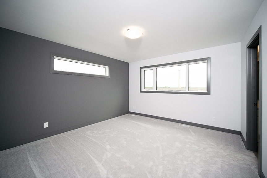 13. Master Bedroom with light grey carpet, dark grey accent wall and dark grey casing and baseboards- 221 Petryk Terrace Broadview Homes DG 15 A