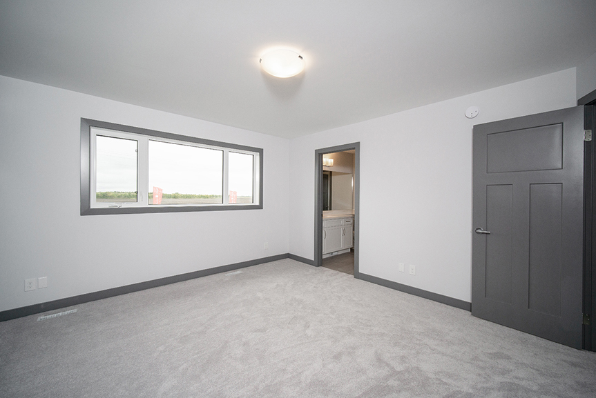 14. Master Bedroom with light grey walls, dark grey casing and grey carpet, and a large 3-piece combination window - 221 Petryk Terrace Broadview Homes DG 15 A