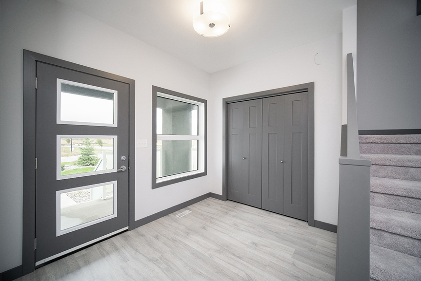 2. Front Foyer with grey vinyl plank flooring, light grey walls, dark grey front door with stacked window inserts and dark grey casing and baseboards - 221 Petryk Terrace Broadview Homes DG 15 A