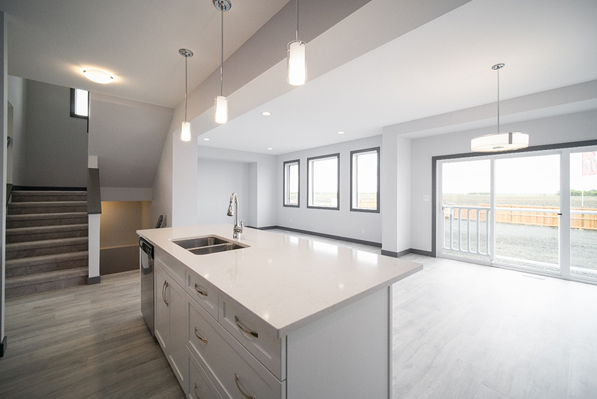 4. Kitchen with white cabinets, white quartz countertops, hanging pendant lights and light grey vinyl plank flooring - 221 Petryk Terrace Broadview Homes DG 15 A