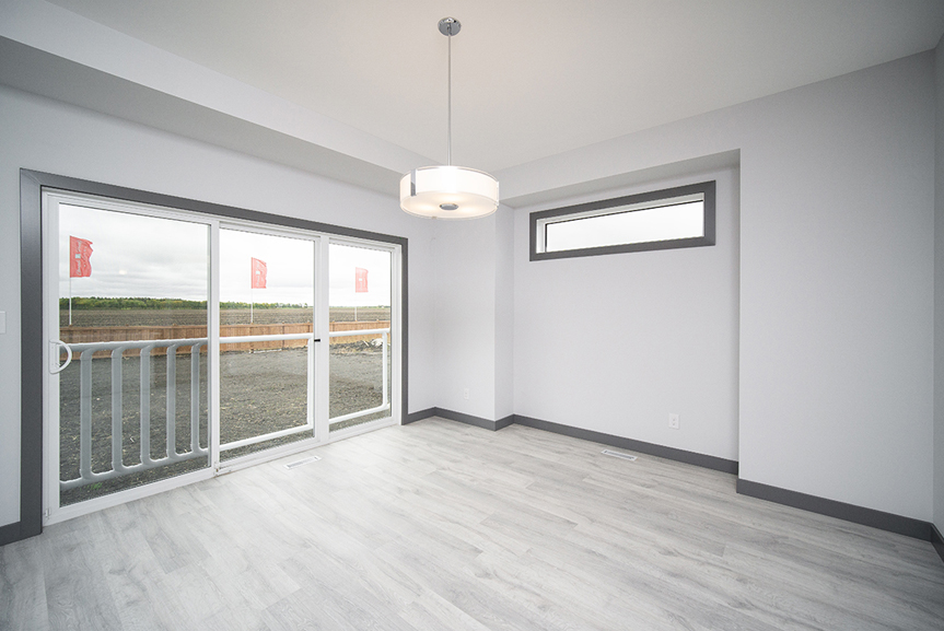 5. Eating Area with triple panel sliding patio door. light grey vinyl plank flooring, light grey walls and dark grey casing and baseboards - 221 Petryk Terrace Broadview Homes DG 15 A
