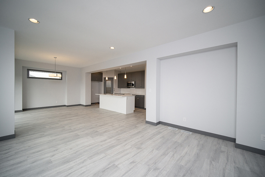 7. Great Room with light grey vinyl plank flooring, dark grey baseboards and light grey walls with drywall cutout- 221 Petryk Terrace Broadview Homes DG 15 A
