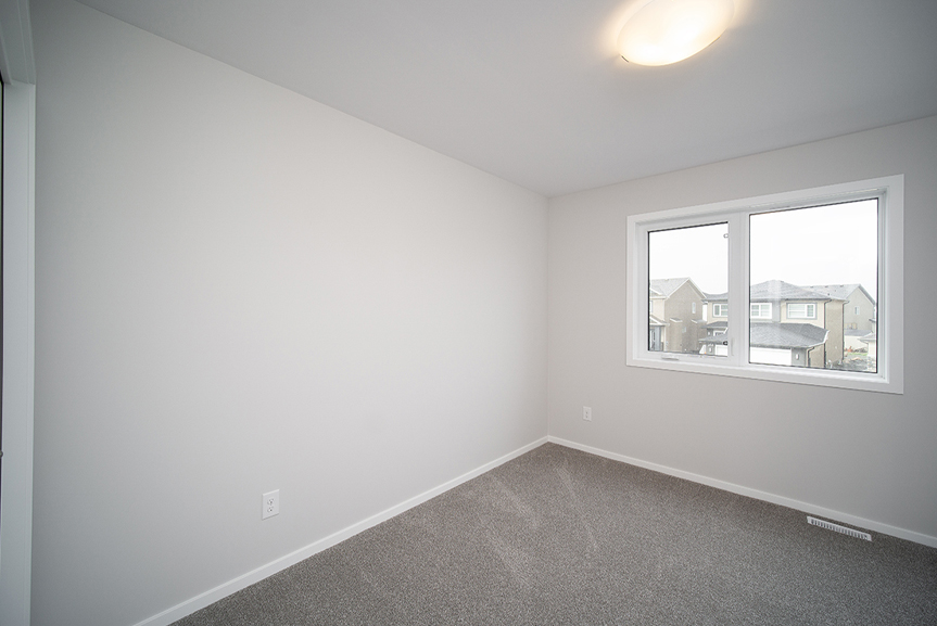 11.  Secondary Bedroom with lush grey carpet, light grey walls and white casing and baseboards  - 247 Joynson Crescent - Broadview Homes The Biscayne DG 14 A