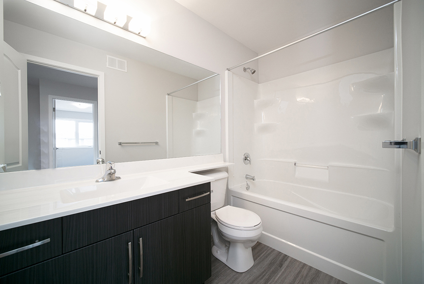 12.  Main Bathroom with grey vinyl plank flooring, dark brown cabinets and white cultured marble vanity top - 247 Joynson Crescent - Broadview Homes The Biscayne DG 14 A