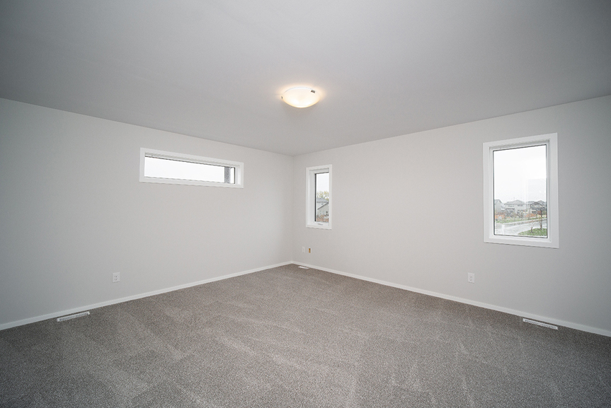 13. Master Bedroom with lush grey carpeting, light grey wals and white window casing - 247 Joynson Crescent - Broadview Homes The Biscayne DG 14 A
