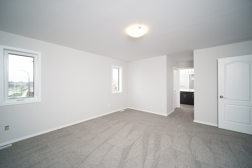 14. Master Bedroom with lush grey  carpet, light grey walls, white window casing and view of the ensuite - 247 Joynson Crescent - Broadview Homes The Biscayne DG 14 A