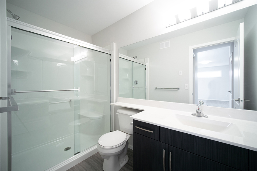 15. Ensuite with grey vinyl plank flooring, dark brown vanity with white cultured marble top and glass and acrylic shower - 247 Joynson Crescent - Broadview Homes The Biscayne DG 14 A