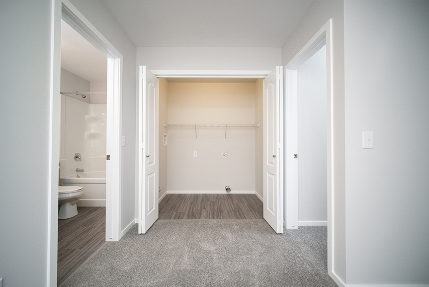 16. Second Floor Laundry with grey vinyl plank flooring, grey carpet, light grey walls and white door casing - 247 Joynson Crescent - Broadview Homes The Biscayne DG 14 A