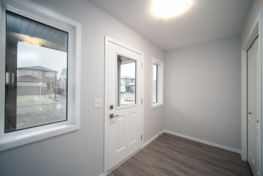 2. Front Foyer with grey vinyl plank flooring, light grey walls, white front door and white window and door casing - 247 Joynson Crescent - Broadview Homes The Biscayne DG 14 A