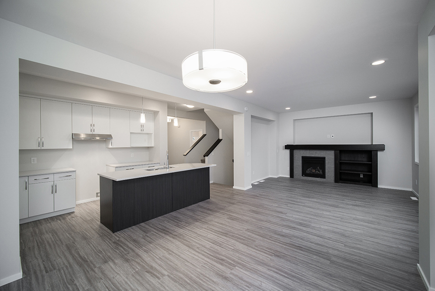 4. Kitchen and Great Room with grey vinyl plank flooring, light grey walls, white cabinets, quartz countertops and fireplace with wood mantle and shelves - 247 Joynson Crescent - Broadview Homes The Biscayne DG 14 A