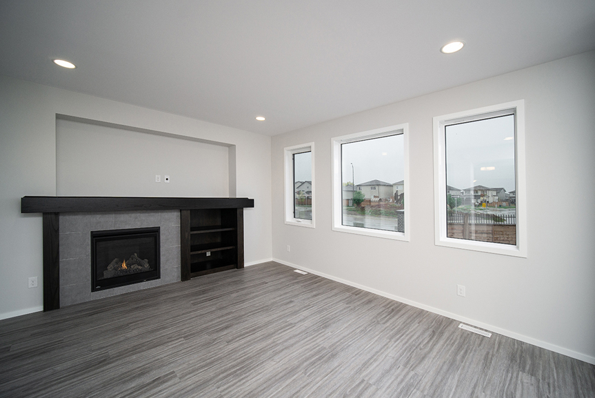 5. Great Room with grey vinyl plank flooring, fireplace and entertainment unit with dark wood mantle and shelves and ceramic tile face, white window casing and light grey walls - 247 Joynson Crescent - Broadview Homes The Biscayne DG 14 A