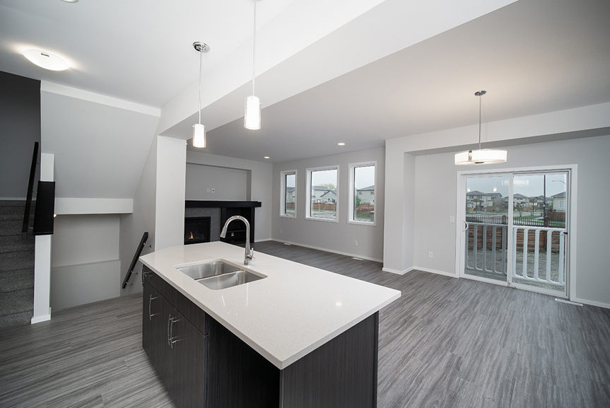 7. Great Room and Eating Area with grey vinyl plank quartz kitchen countertops and fireplace with wood mantle and shelves- 247 Joynson Crescent - Broadview Homes The Biscayne DG 14 A