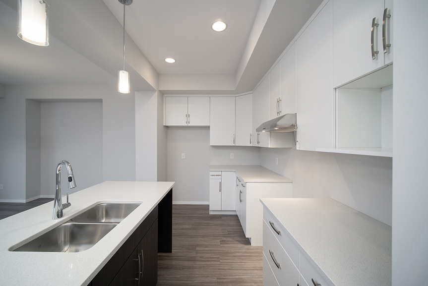 8. Kitchen with grey vinyl plank flooring, white cabinets and white quartz countertops - 247 Joynson Crescent - Broadview Homes The Biscayne DG 14 A