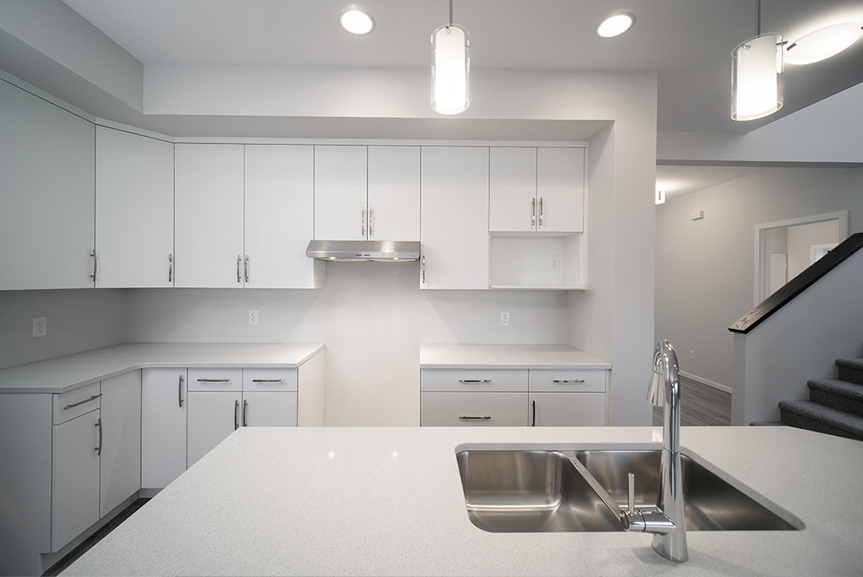 9. Kitchen with white cabinets, white quartz countertops, chrome hardware and hanging pendant lights  - 247 Joynson Crescent - Broadview Homes The Biscayne DG 14 A