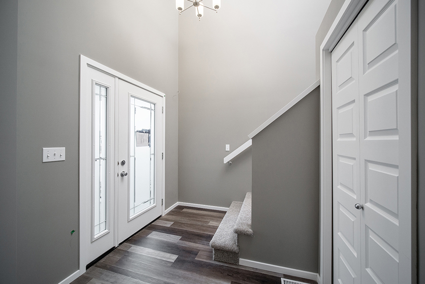1. Front Foyer with chateau brown vinyl plank flooring, grey walls, white baseboards and white door trim - 34 Grey Heron The Aurora DG 9 C Broadview Homes