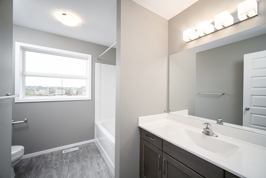 12. Main Bathroom with grey vinyl flooring, maple winter vanity with white cultured marble vanity top, light grey walls and white baseboards and window casing - 34 Grey Heron The Aurora DG 9 C Broadview Homes