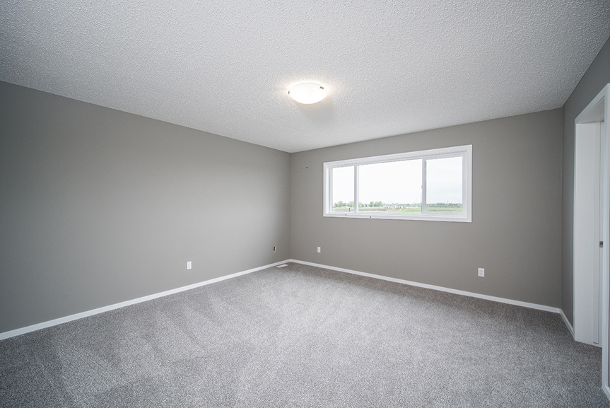 15. Master Bedroom with grey carpet, white baseboards, white window casing and grey walls- 34 Grey Heron The Aurora DG 9 C Broadview Homes