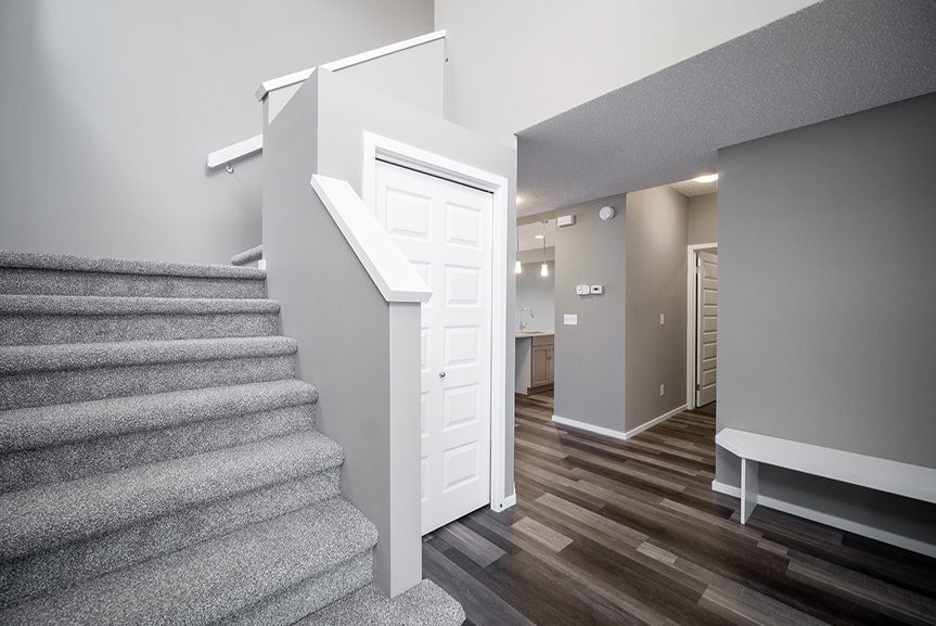 2. Front Foyer with grey carpet on stairs, chateau brown vinyl plank flooring, grey walls and white built-in bench and stubwall caps  - 34 Grey Heron The Aurora DG 9 C Broadview Homes