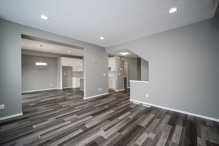 3. Great Room with chateau brown vinyl plank flooring, white baseboards and grey walls - 34 Grey Heron The Aurora DG 9 C Broadview Homes