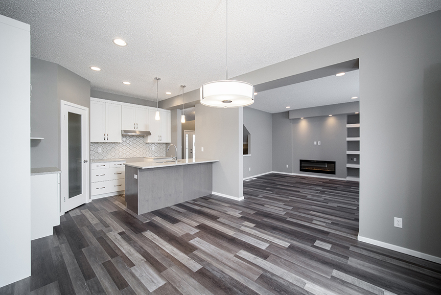 4. Great Room and Kitchen with chateau brown vinyl plank flooring, grey walls, white baseboards and white cabinets  - 34 Grey Heron The Aurora DG 9 C Broadview Homes