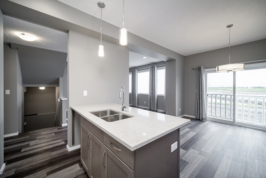 6. Kitchen with maple winter island, white quartz countertops, grey walls, chateau brown vinyl plank flooring and hanging pendant lights - 34 Grey Heron The Aurora DG 9 C Broadview Homes