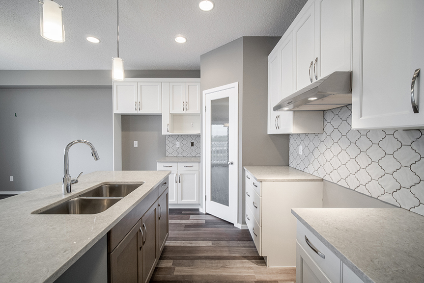 7. Kitchen with white maple cabinets, ceramic tile backsplash, maple winter island with quartz countertops and chateau brown vinyl plank flooring  - 34 Grey Heron The Aurora DG 9 C Broadview Homes