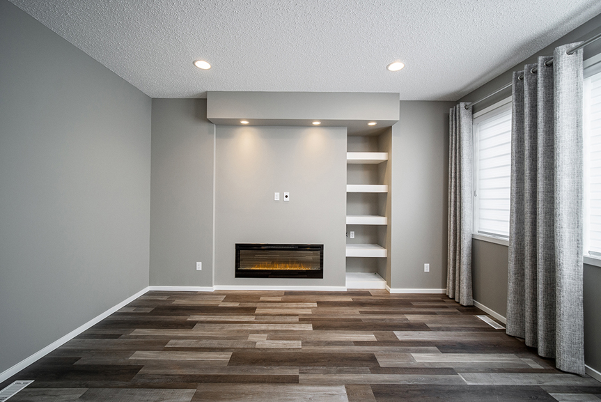8. Great Room with Fireplace, white shelving, light grey walls, white baseboards, grey curtains and chateau brown vinyl plank flooring - 34 Grey Heron The Aurora DG 9 C Broadview Homes