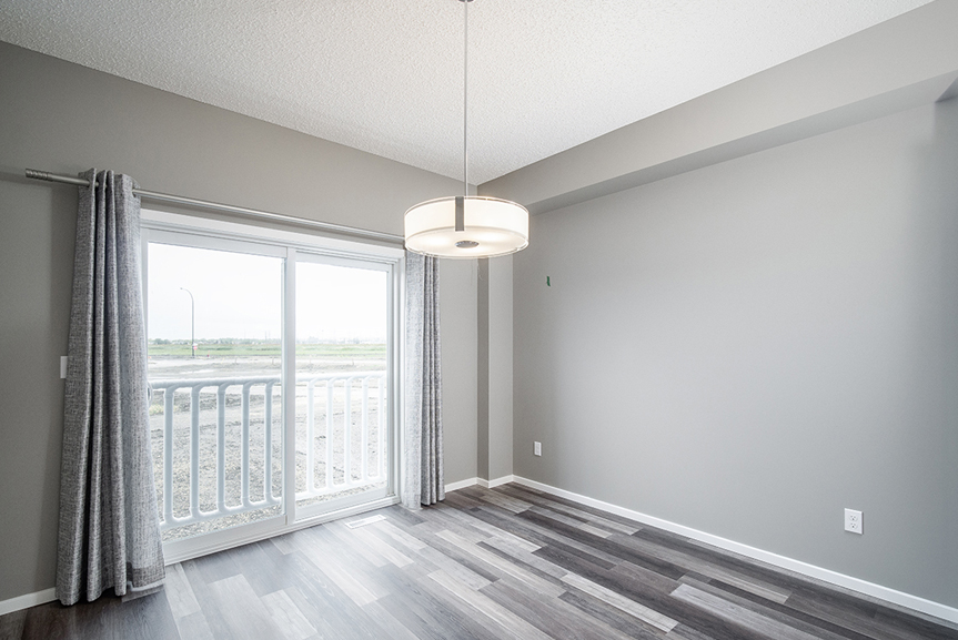 9. Eating Area with chateau brown vinyl plank flooring, light grey walls, sliding patio door and white baseboards - 34 Grey Heron The Aurora DG 9 C Broadview Homes