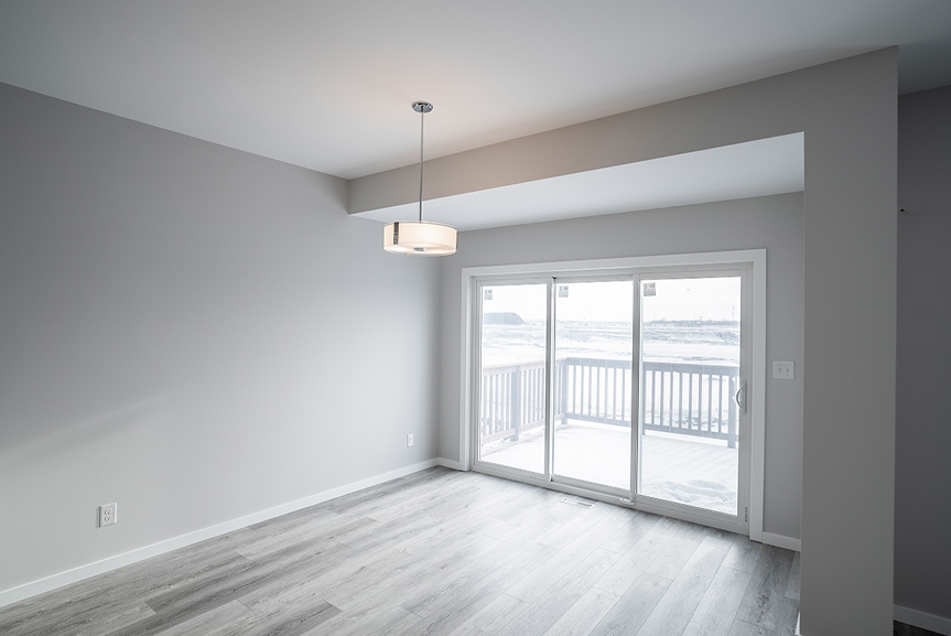 11. Dining Room with light grey vinyl plank flooring, light grey painted walls, triple panel patio door and white casing and baseboards - 62 Jack Reimer DG 18 C The Cottonwood Broadview Homes