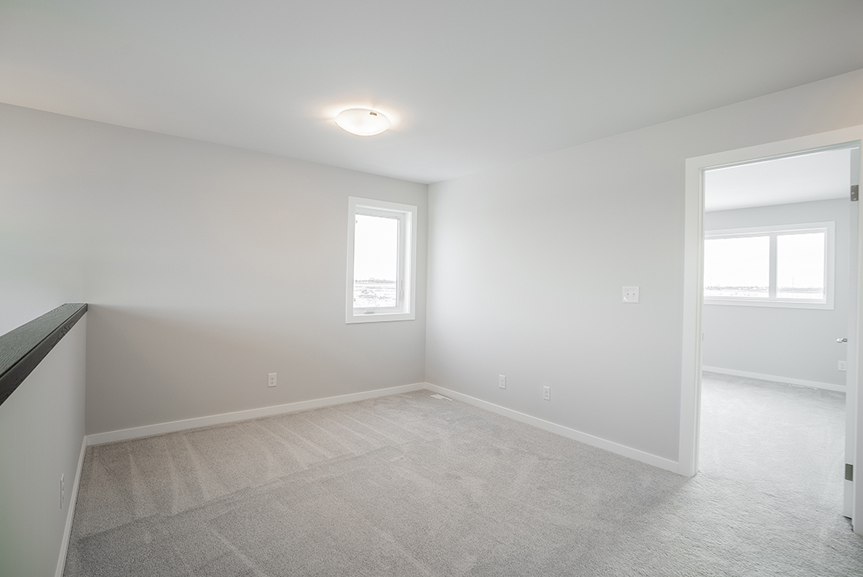 14. Second Floor Loft - 62 Jack Reimer DG 18 C The Cottonwood Broadview Homes with light grey painted walls, grey carpet and white casing and baseboards