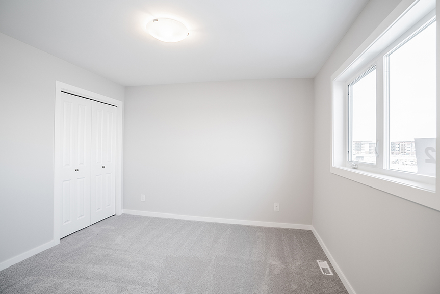 15. Secondary Bedroom with light grey painted walls, grey carpet, and white casing and baseboards  - 62 Jack Reimer DG 18 C The Cottonwood Broadview Homes