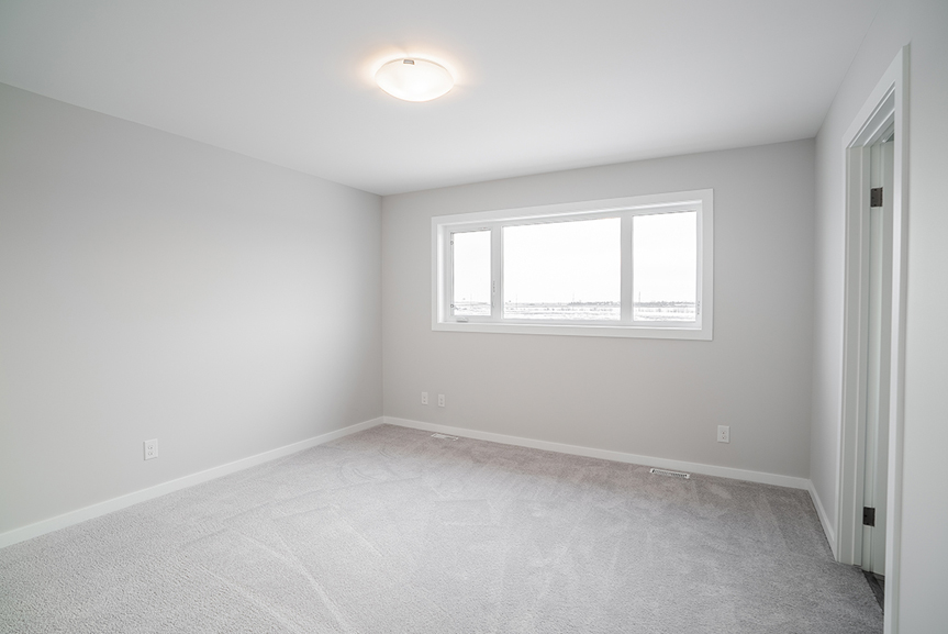 16. Master Bedroom with light grey painted walls, grey carpet, large window and white casing and baseboards  - 62 Jack Reimer DG 18 C The Cottonwood Broadview Homes