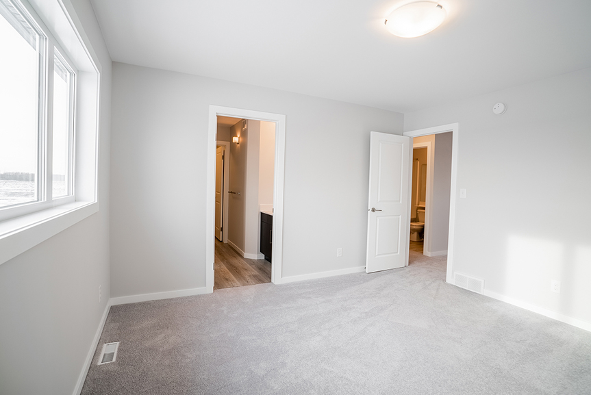 17. Master Bedroom with light grey painted walls, grey carpet and white casing and baseboards - 62 Jack Reimer DG 18 C The Cottonwood Broadview Homes