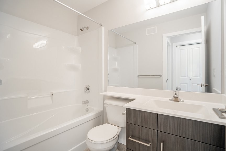 20. Main Bathroom with woodgrain vanity, acrylic tub and shower, white cultured marble vanity tops and light grey painted walls- 62 Jack Reimer DG 18 C The Cottonwood Broadview Homes
