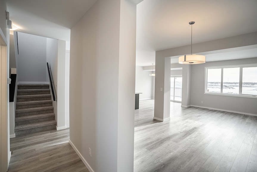 3. Dining and Hall with light grey painted walls, vinyl plank flooring, white casing and baseboards and dark wood stubwall caps - 62 Jack Reimer DG 18 C The Cottonwood Broadview Homes
