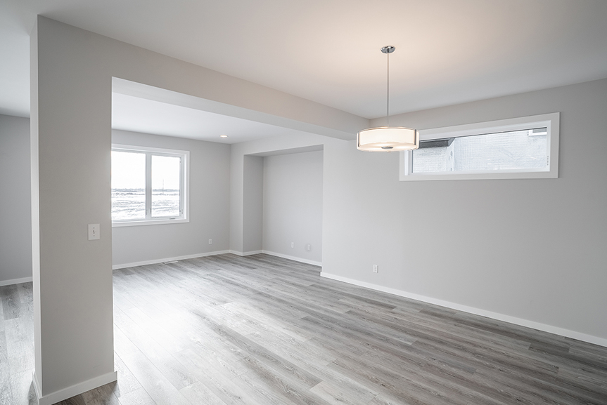 5. Dining and Great Room with grey vinyl plank flooring, light grey painted walls, and white casing and baseboards - 62 Jack Reimer DG 18 C The Cottonwood Broadview Homes