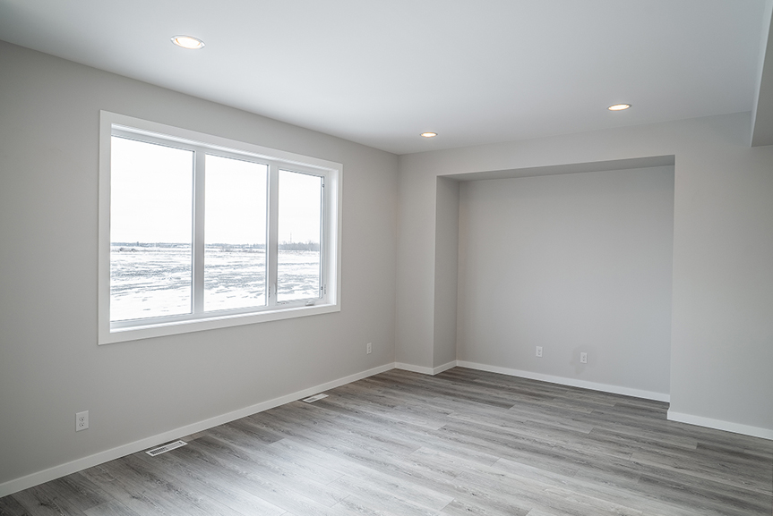 6. Great Room - 62 Jack Reimer DG 18 C The Cottonwood Broadview Homes with grey vinyl plank flooring, light grey painted walls, white casing and baseboards and large window