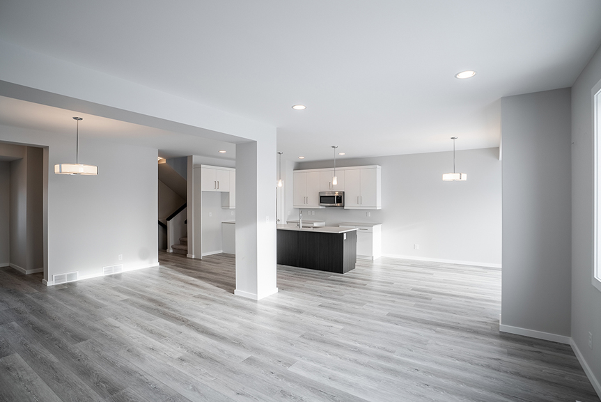 7. Kitchen and great room with grey vinyl plank flooring, light grey painted walls, dark woodgrain island and white kitchen cabinets  - 62 Jack Reimer DG 18 C The Cottonwood Broadview Homes