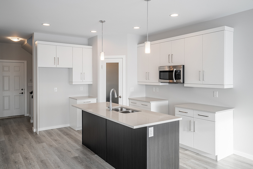 8. Kitchen with grey vinyl plank flooring, dark woodgrain island, white kitchen cabinets, quartz kitchen countertops and light grey painted walls- 62 Jack Reimer DG 18 C The Cottonwood Broadview Homes