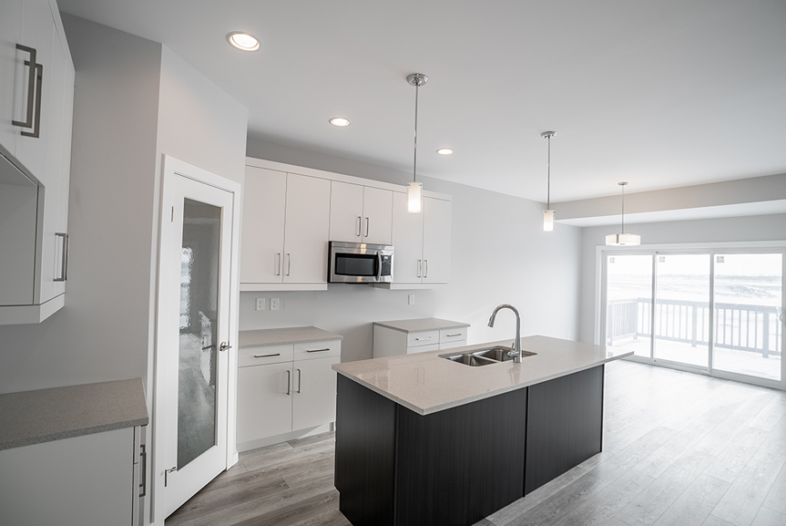 9. Kitchen with grey vinyl plank flooring, dark woodgrain island, quartz countertops and white cabinets  - 62 Jack Reimer DG 18 C The Cottonwood Broadview Homes